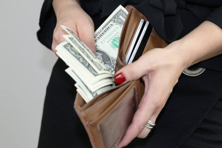 אישה מוציאה כסף מארנק